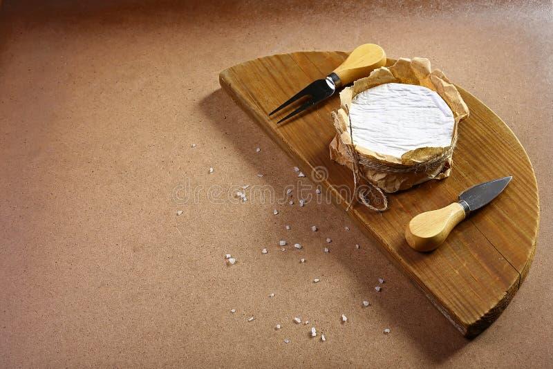 Käsecamembert oder -briekäse auf hölzernem Brett mit Käse-Vorlegemesser Heller hölzerner Hintergrund Milchproduktion Flache Lage  lizenzfreie stockbilder