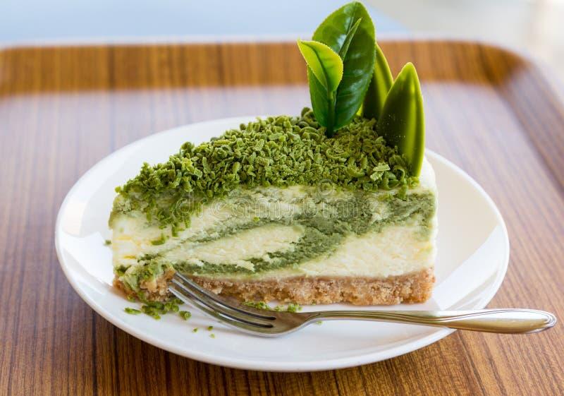 Käsekuchen des grünen Tees auf weißem Teller mit Gabel stockfotos