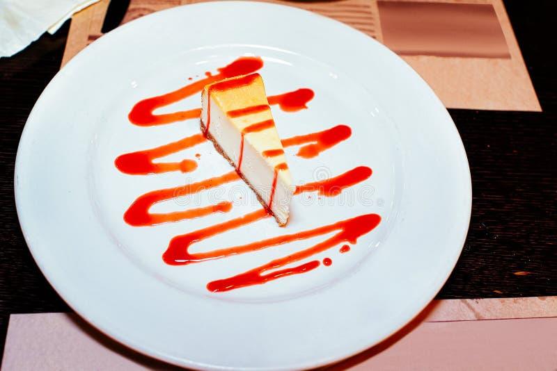 Käsekuchen mit Erdbeere-toppinng Soße auf weißer Platte in einem Restaurant stockbilder