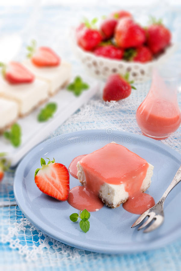 Käsekuchen mit Erdbeeresoße stockbilder