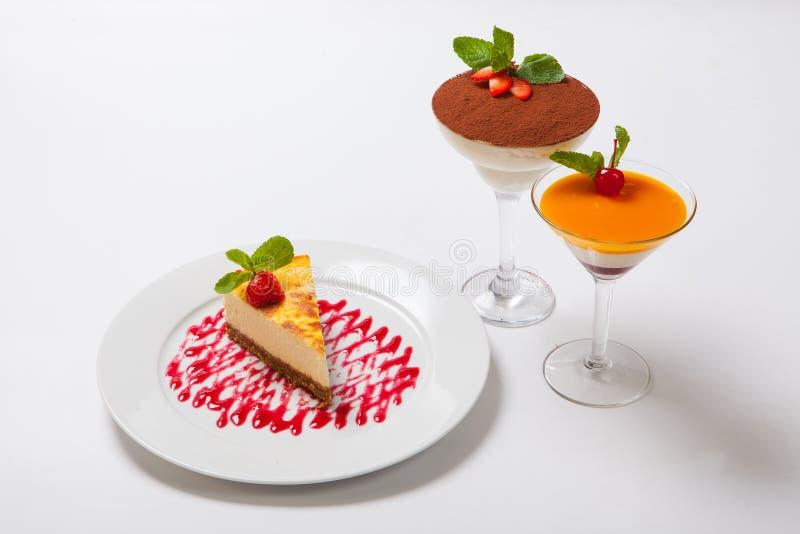 Käsekuchen mit frischen Erdbeeren auf weißer Platte stockbilder