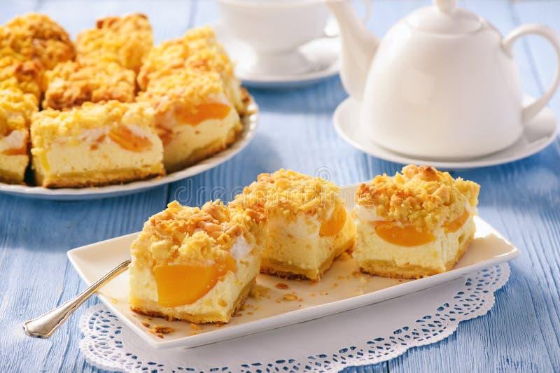 Käsekuchen mit Pfirsichen auf blauem hölzernem Hintergrund stockfotografie