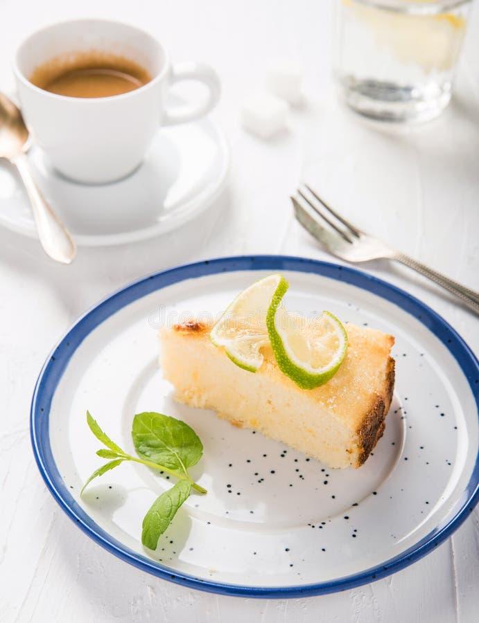 Käsekuchen mit Ricottakäse auf einer schönen Platte, Weinlesegabel, einer Schale aromatischem Espresso und Wasser mit Zitrone lizenzfreies stockfoto