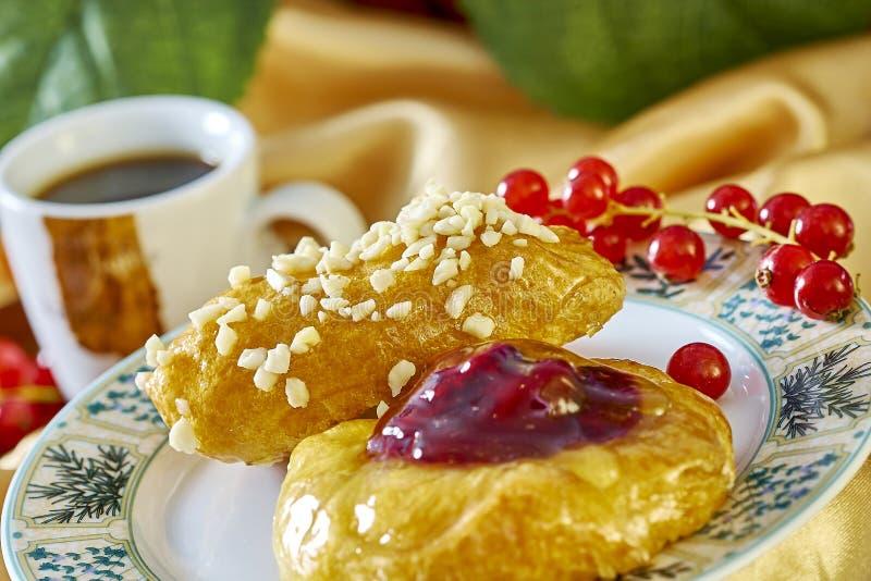 Käsekuchen mit Stau auf einer Platte vor dem hintergrund der Schale mit einem Zweig des vollen kochenden Lebensmittels der rote J lizenzfreie stockfotografie