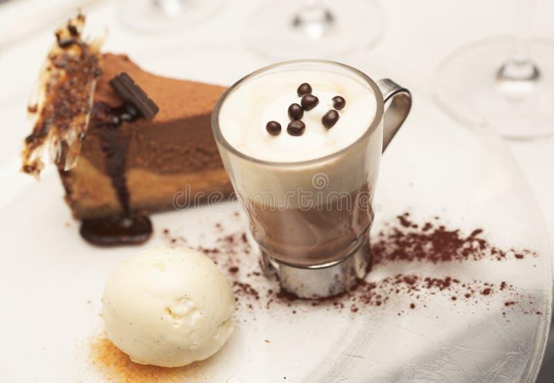 Käsekuchen mit Vanilleeiscreme und heißer Kakao stockfotografie