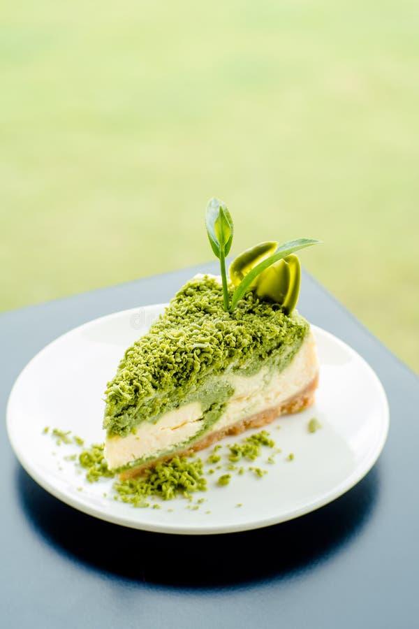 Käsekuchennachtisch des grünen Tees auf weißem Teller lizenzfreies stockbild