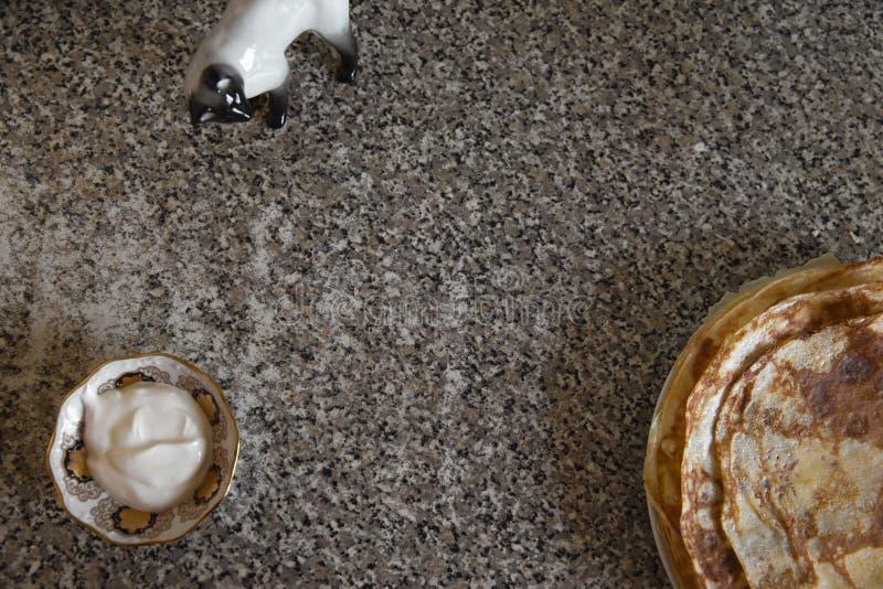 Käsepfannkuchen mit Sahne kithcen an Tabelle und eine Katzenporzellanstatue lizenzfreie stockbilder