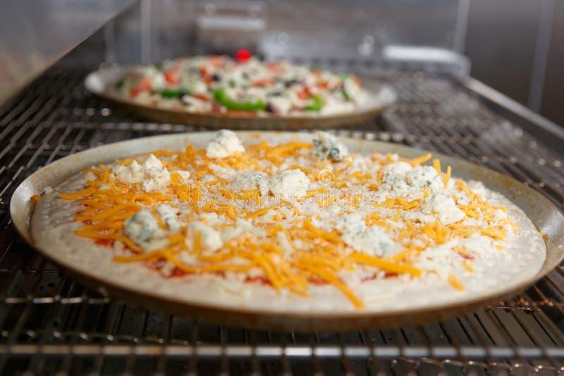 Käsepizza, die den industriellen Ofen kommt lizenzfreie stockfotos