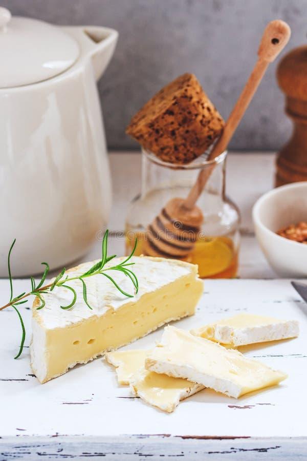 Käseplatte diente mit Crackern, Honig und Nüssen Camembert auf weißem hölzernem Umhüllungsbrett über weißem Beschaffenheitshinter lizenzfreie stockbilder