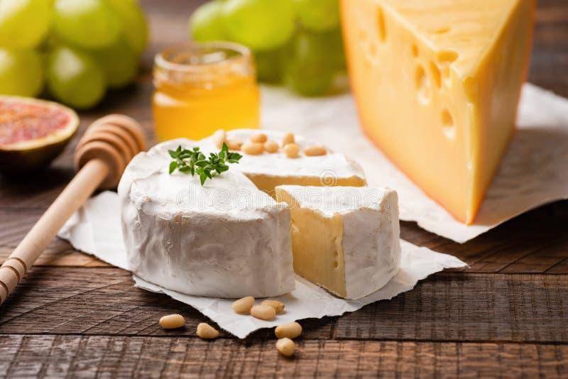 Käseplatte mit Briekäse, Camembert, maasdam Käse und Früchten stockfotografie