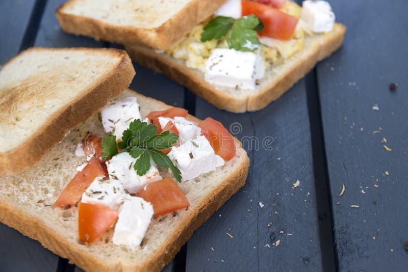 Käsesandwiche, Tomate, Grüns, Brot, dunkler hölzerner Hintergrund, Nahrung lizenzfreies stockbild