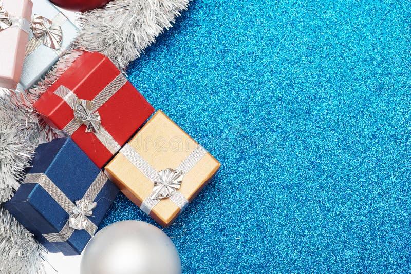 Kästchen für Geschenk, Weihnachtsball und Weihnachtslametta auf Blau lizenzfreie stockbilder