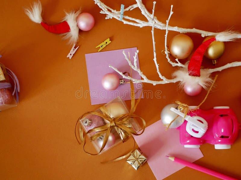 Kästen mit Bällen, Geschenke, rosa Plastikautospielzeug, Weihnachtsdekor auf einem hellen Hintergrund stockbild