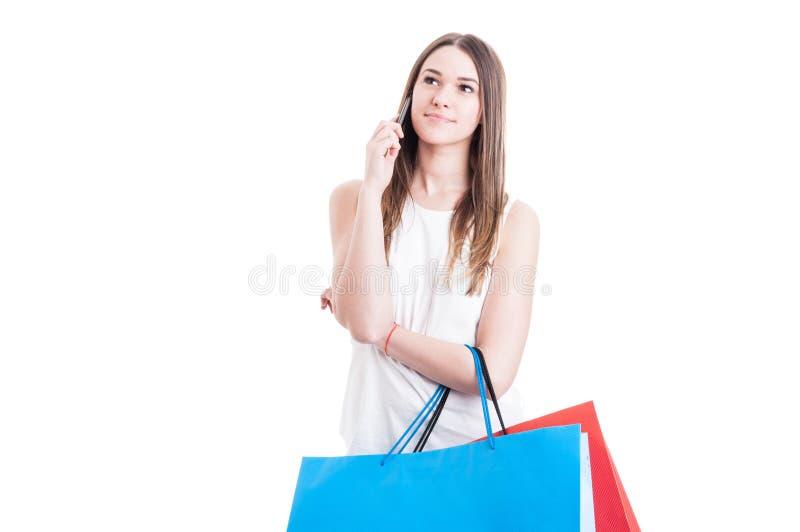 Käufer der jungen Frau, der am Telefon spricht und weg schaut stockbilder