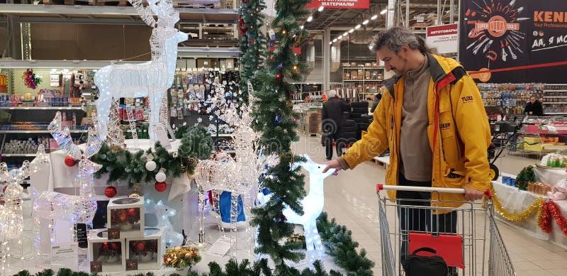 Käufer wählt Weihnachtszahlen und -dekorationen im Speicher vor lizenzfreie stockbilder