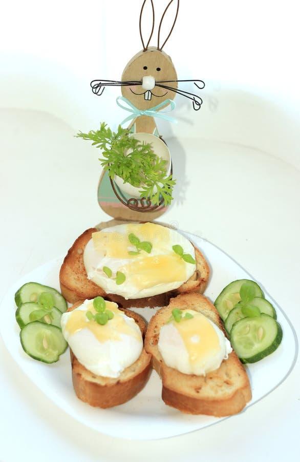 Kłusujący jajka na wznoszących toast baguette plasterkach z ogórkiem na białym talerzu z zając która trzyma sprig pietruszka fotografia stock