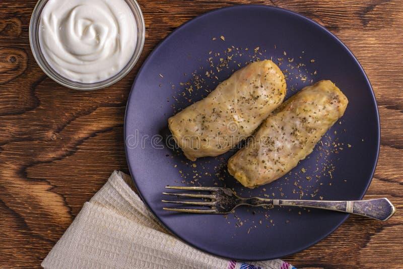 kålrullar som stoppades med jordnötkött och ris, tjänade som på en vit platta på en gammal lantlig tabell med gräddfil i en bunke arkivfoto