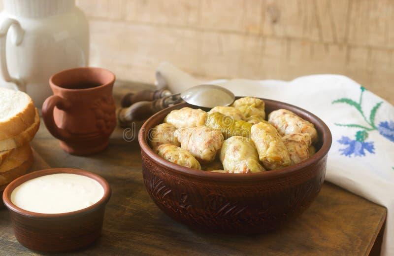 Kålrullar tjänade som med gräddfil, bröd och vin Dolma, sarma, sarmale, golubtsy eller golabki royaltyfri foto