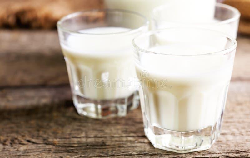 Kózki mleko w szkłach, rocznika drewniany tło, selekcyjna ostrość obrazy royalty free