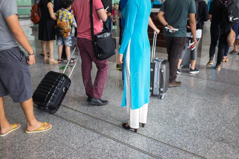 Kö av folk i den Noi Bai flygplatsen, Vietnam Fokusera på den kvinnliga personalen som bär den vietnamesiska långa klänningen Ao  arkivfoto