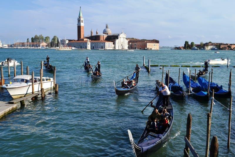Kö av gondoler som flyttar sig inom staden med många turister i Venedig royaltyfria bilder