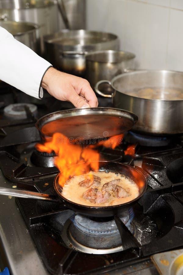 kök för kockmaträttflambe som gör restaurangen arkivbilder