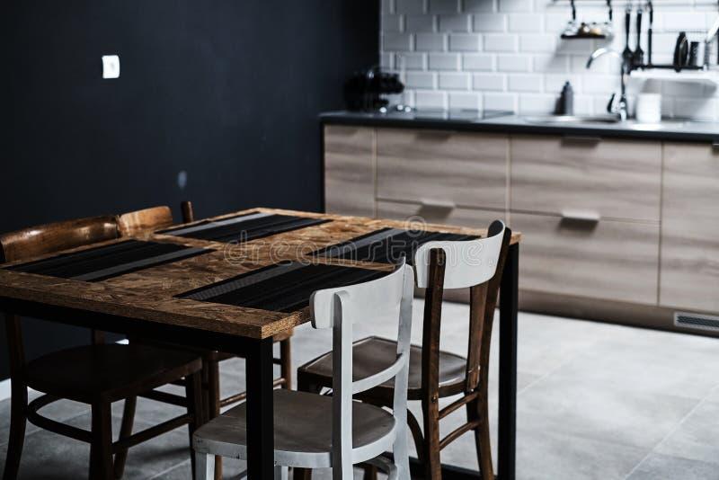 Kök i en vindstil med betong och tegelstenväggar och tegelplattor Det finns ett svart köksbord med vita stolar arkivfoto