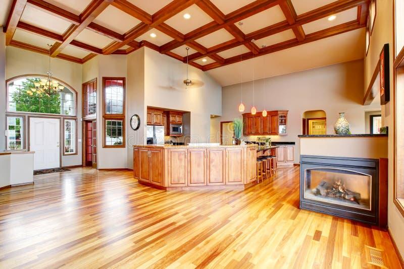 Kök och vardagsrum med ädelträgolvet, vit ingångsdörr arkivfoton