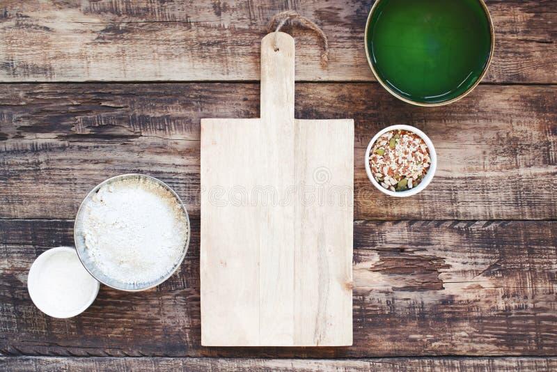 Kökbakgrund med den tomma gamla träskärbrädan och organiska ingredienser arkivbilder