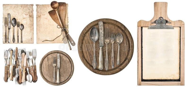 Kökbräde, åldrigt receptpapper, svart tavla och tappningbestick arkivfoto