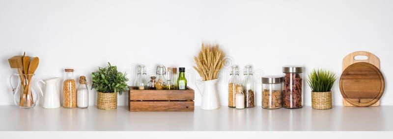 Kökhylla med olika örter, kryddor, redskap på vit bakgrund arkivbilder