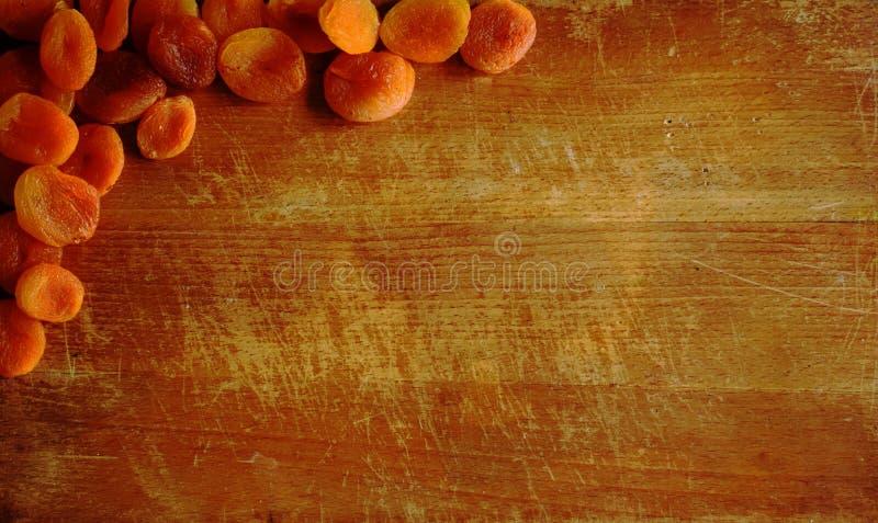 Kökklippplanka med torkade aprikors fotografering för bildbyråer