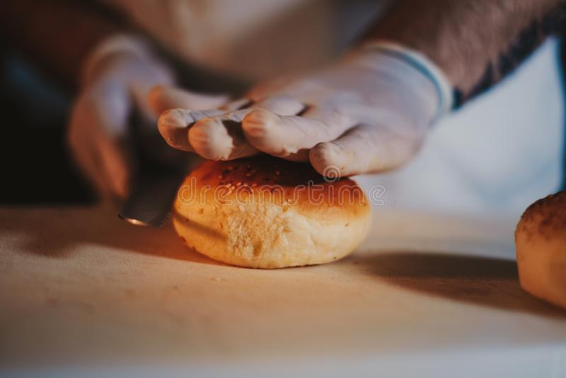 Kökkockstart som klipper hamburgarebullen med en kniv arkivfoto