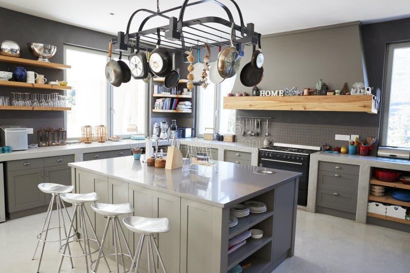 Kökområde av den moderna hemmiljön med ön och anordningar royaltyfria bilder