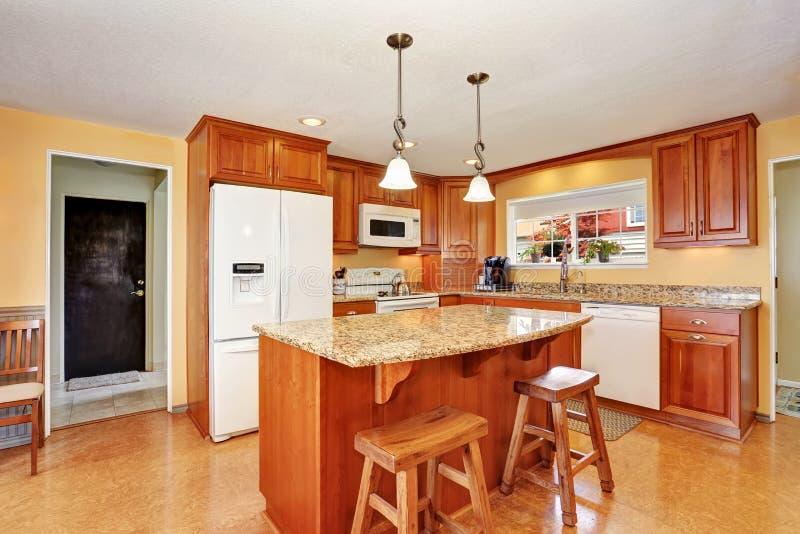 Kökruminre med ön, träkabinetter och graniträknareöverkanten royaltyfri foto