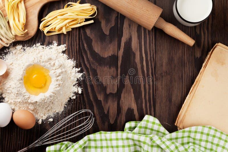 Köksbord med receptboken, redskap och ingredienser royaltyfria bilder