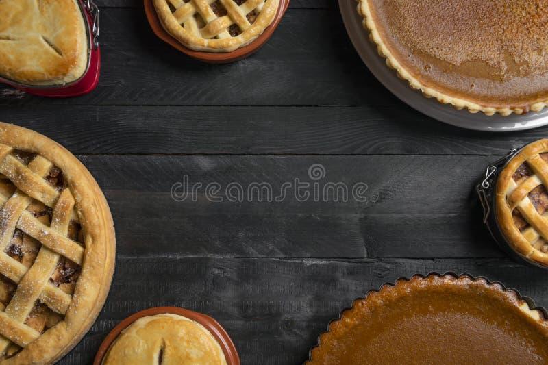 Köksbord mycket av olika pajer, pumpapajer, äppelpajer, med tomt utrymme i mitt Traditionell ferieefterrätt royaltyfri foto