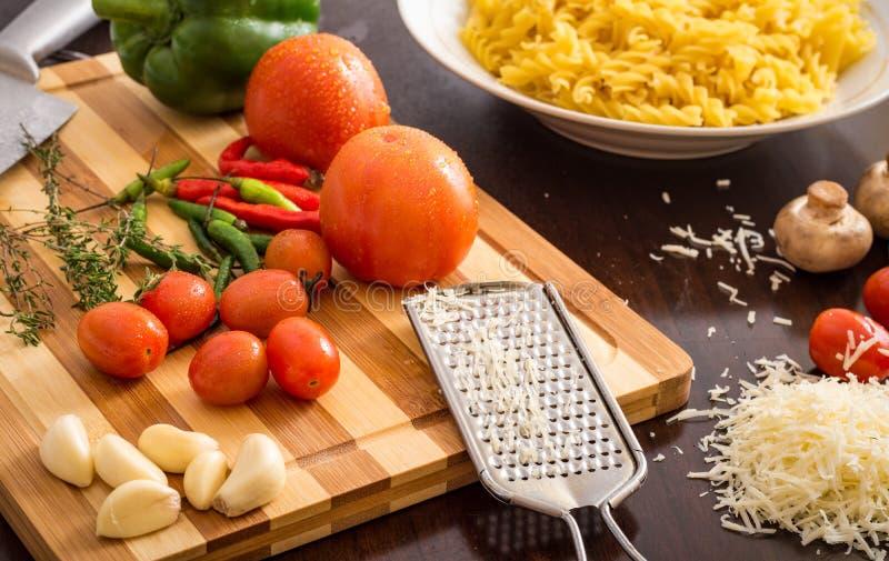 Köksbordförberedelse med pasta och ingredienser på skärbräda arkivbild