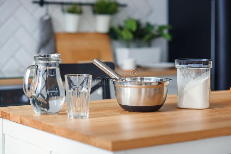 Köksgeråd för degförberedelse En bank med vatten, en metallplatta och ett mjöl arkivfoto