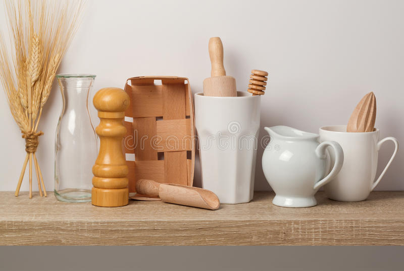 Köksgeråd och dishware på trähylla royaltyfri foto