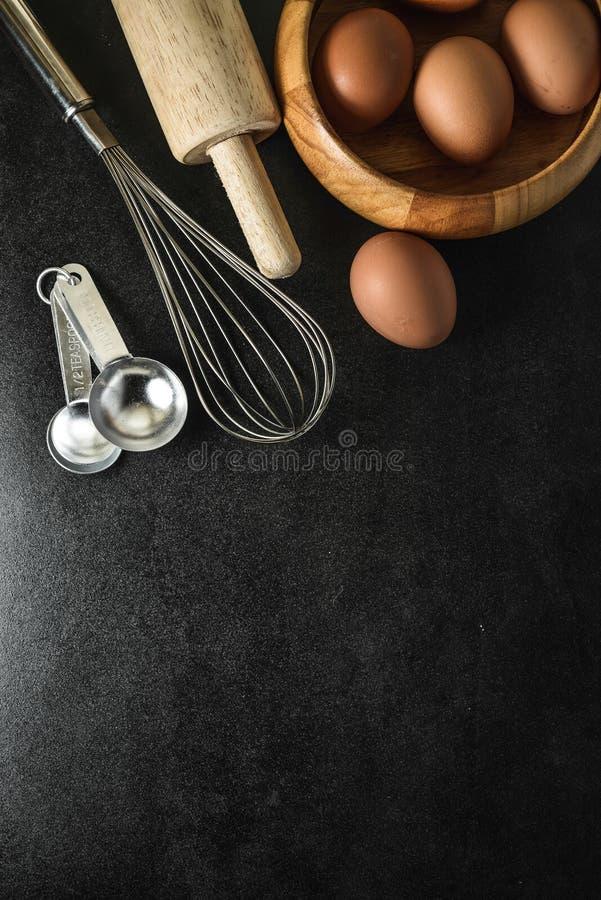 Köksgeråd och stekheta ingredienser: ägg och mjöl på svart bakgrund, kopia-utrymme fotografering för bildbyråer
