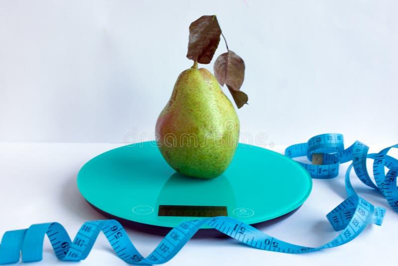 Kökskala, päron och meter på vit tabellbakgrund arkivfoton
