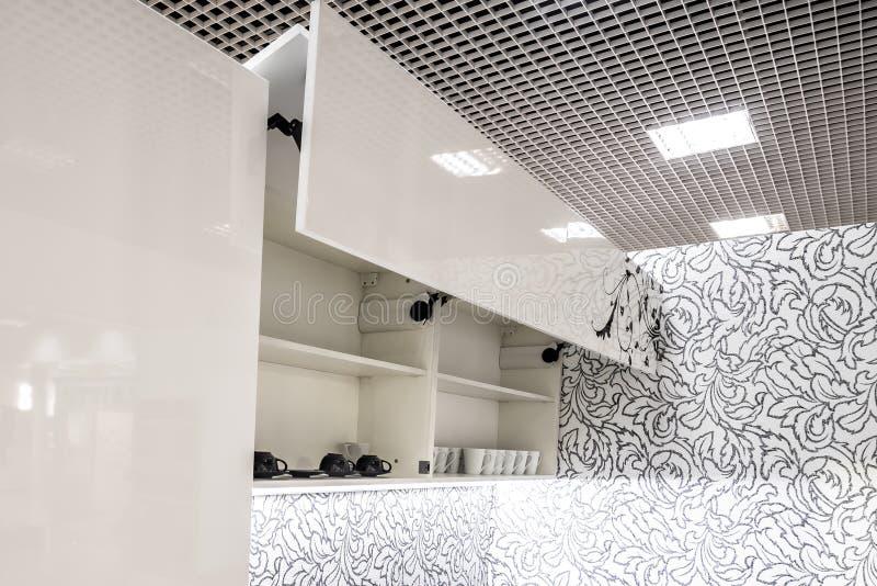 Köksskåp med öppnade framdelar med maträtthållarehyllor inom Elevatorsystem för bi-veck framdelar för direkt tillträde i kök royaltyfri foto