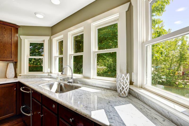 Köksskåp med den marmoröverkanten och vasken royaltyfria foton