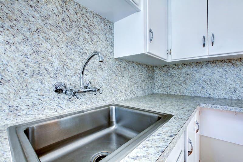 Köksskåp med stålvasken och graniträknareöverkanten royaltyfri fotografi
