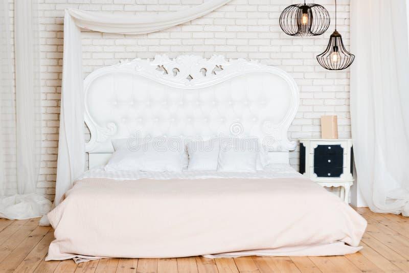 Königgrößenbett in der Dachbodenwohnung Dachbodenartschlafzimmer mit weißem Entwurf stockfoto