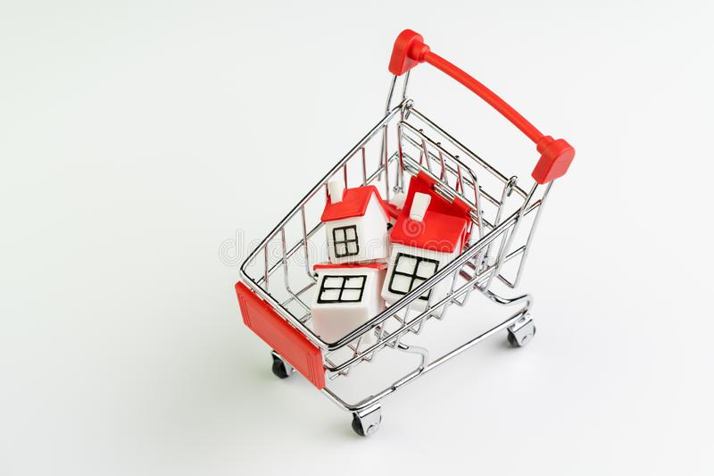 Köp- och försäljningshus, egenskapstillgång och efterfrågan på fastigheten som inhandlar begrepp, shoppingvagn eller spårvagn med royaltyfria foton
