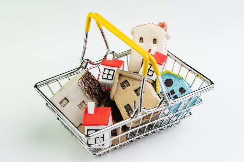 K?p och f?rs?ljningshus eller fastighet som inhandlar begreppet, shoppingkorg med fullt av sm? gulliga miniatyrhus p? vit bakgrun royaltyfri bild
