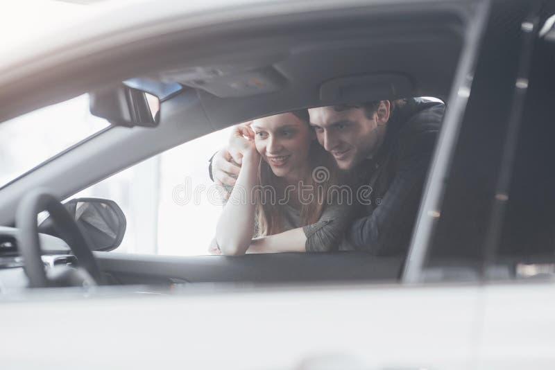 Köpa deras första bil tillsammans Sikt för hög vinkel av det unga bilförsäljareanseendet på återförsäljaren som berättar om royaltyfri fotografi