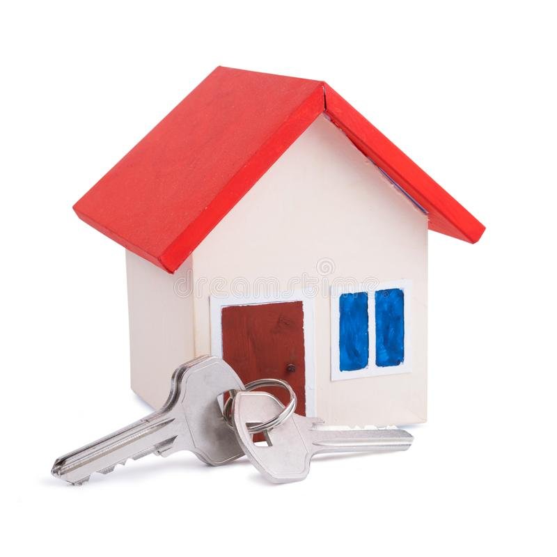 Köpa eller sälja begrepp av ett hus med det röda taket och en tangent som isoleras på vit bakgrund royaltyfri foto